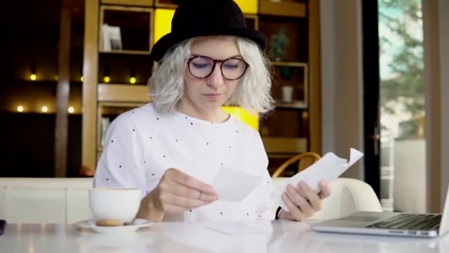 vídeos y material grabado en eventos de stock de dinero y planificación financiera, comprobación de facturas con el ordenador portátil de la mujer - planificación financiera