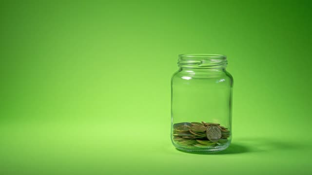 Money coin in glass bottle growing money Time lapse of money coin in glass bottle growing growth saving money. Concept financial business investment. Green background. 4K jar stock videos & royalty-free footage