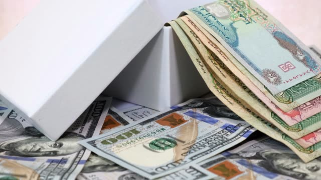 UAE Money Dirhams in White Gift Box on a Background of USA Dollars Banknotes on Rotating Table. Global Business Concept.