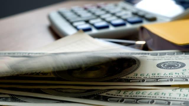 stockvideo's en b-roll-footage met geld valt op een office-tabel. us dollars rekeningen en rekenmachine. financiën en besparingen concept. - aandelen
