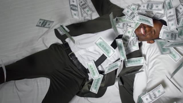 money falling on businessman in bed - dollar bill стоковые видео и кадры b-roll