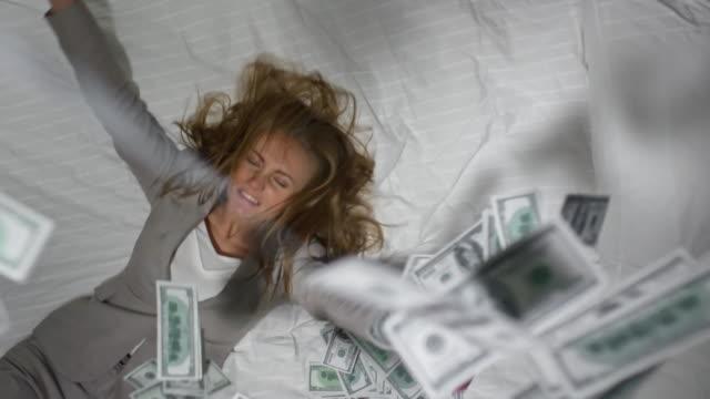 money falling on ecstatic businesswoman in bed - dollar bill стоковые видео и кадры b-roll