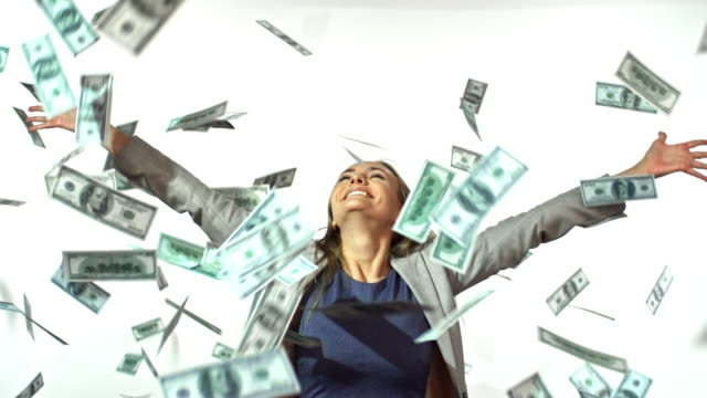 Money Falling on Happy Businesswoman Slowmo of happy businesswoman laughing and jumping against studio backdrop as money falling from above paper currency stock videos & royalty-free footage