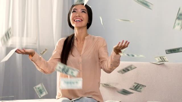 Money falling on happy shopaholic woman enjoying cash back service, slow motion