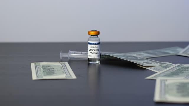 pieniądze spadające na fiolki ze szczepionką coronavirus - covid vaccine filmów i materiałów b-roll