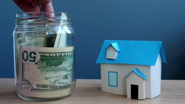 Dinero para la casa. Mano poner billetes de un dólar en tarro y modelo de casa. - vídeo