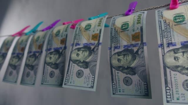 penningtvättskoncept. dollarsedlar torkas på ett rep. rena pengar. - dirty money bildbanksvideor och videomaterial från bakom kulisserna