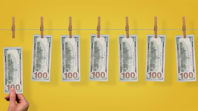 $100 Money line, back side of $100 dollar bills on yellow background