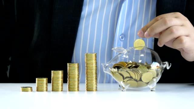 돈 절약, 비즈니스, 은행, 투자, 금융 및 생명 보험 개념-슬로우 모션 젊은 사업가 미래의 사업 계획과 금융 생활에 대 한 투자에 돈을 절약 하기 위해 돼지 저금통 유리에 황금 동전을 떨어 - 이율 스톡 비디오 및 b-롤 화면