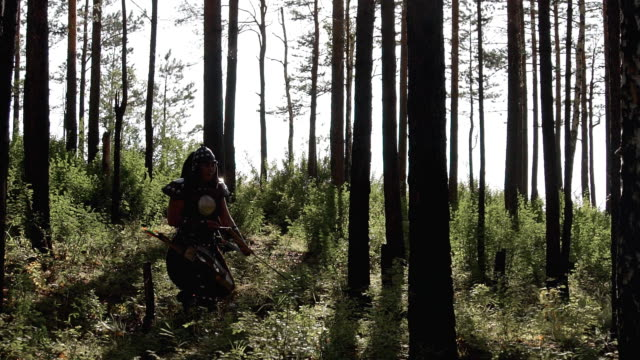 Mongolian archer makes way through dense forest with weapons video