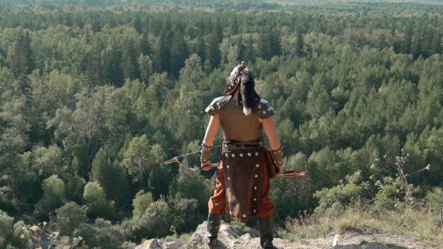 mongolischer bogenschütze steht am rand des berges an sonnigen tag - sportchampion stock-videos und b-roll-filmmaterial