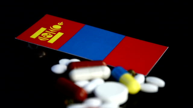 Mongolian flag with lot of medical pills isolated on black background video