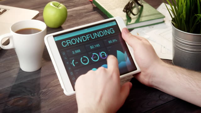 Monitoring crowdfunding data using tablet computer at desk video