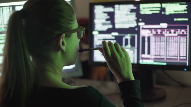 Monitors woman hand play Stock 4k clip of a young woman contemplating two computer monitors, she is illuminated by the colored lights from a peripheral screen image as she plays with her hand & pen. human age stock videos & royalty-free footage
