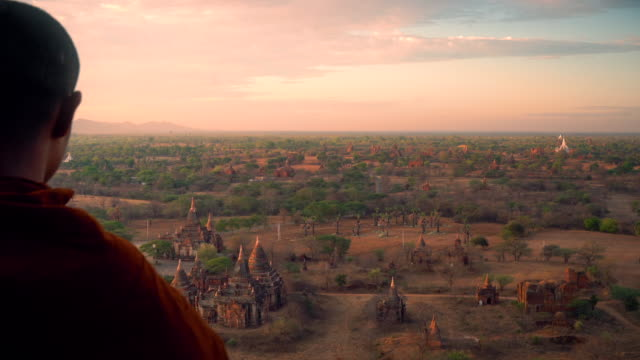 Monk enjoy the view of landscape of pagoda Monk enjoy the view of landscape of pagoda at Bagan, Myanmar in morning. myanmar stock videos & royalty-free footage