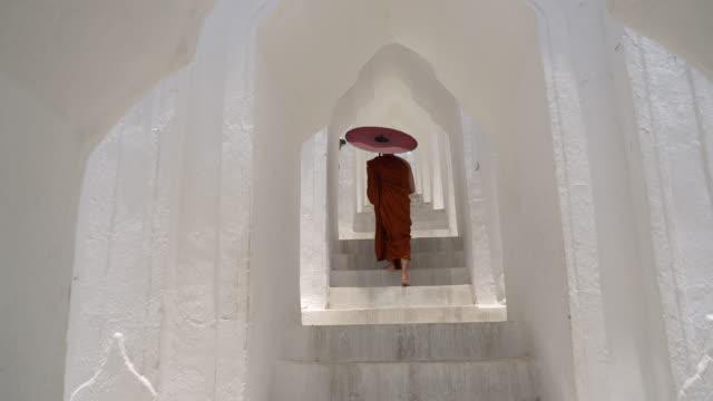 Monk make a merit with umbrella Monk make a merit with umbrella at Hsinbyume Pagoda in Mingun Mandaley, Myanmar. bagan stock videos & royalty-free footage