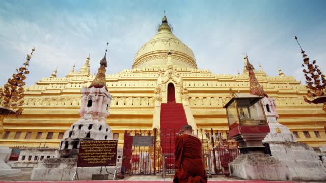 monk make merrit at gloden shwezigon pagoda - myanmar video stock e b–roll