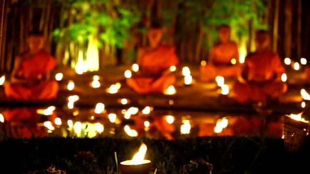 vídeos y material grabado en eventos de stock de monje la meditación en templo con luz de las velas por la noche - hermano