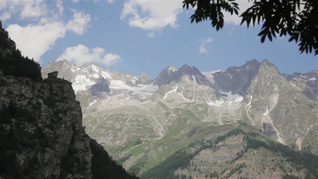 mont blanc mountain massif valley view little snow on top clouds sky windy. scenic summer landscape glacier covered spring waterfall trails seen from northern italian side courmayeur town, aosta - courmayeur estate video stock e b–roll