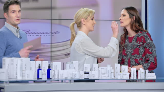 Montage: Woman placing some lip salve of the cosmetic line she is presenting on the female model's lips while talking to the male host of the infomercial show Montage of clips edited to look like an infomercial of a female presenting a cosmetic line talking to the male host while placing some lip salve onto the lips of the female model. Shot in Slovenia. lip balm stock videos & royalty-free footage