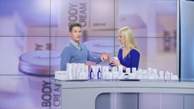 Montage: Woman presenting a cosmetic line on an infomercial show rubbing some cream onto the back of the male host's hand as they talk