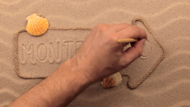 Montenegro inscription written by hand on the sand, in the pointer made from rope. video