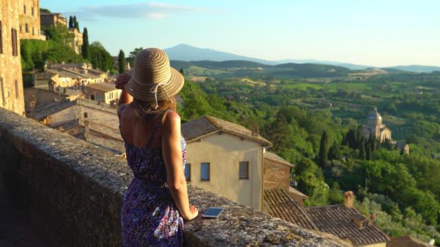 montepulciano, toskana, i̇talya, şehir ve kırsal balkonundan manzara kız bakar - toskana stok videoları ve detay görüntü çekimi
