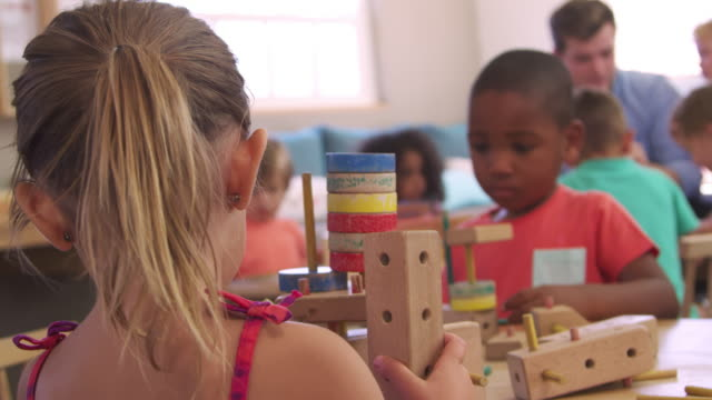 Montessori School Pupils Work At Desk With Wooden Building Set Montessori School Pupils Work At Desk With Wooden Building Set child care stock videos & royalty-free footage