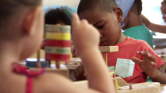 stockvideo's en b-roll-footage met montessori school leerlingen werken bij bureau met houten bouw set - peuterklasleeftijd