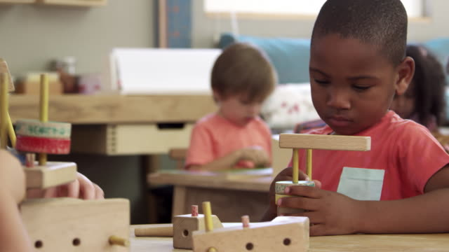 Montessori School Pupils Work At Desk With Wooden Building Set video