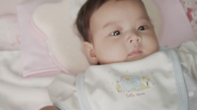 A 5 Month Asian Baby Girl sleeping on her bed at home