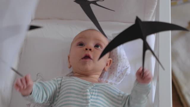 vídeos de stock, filmes e b-roll de bebê idoso do mês que ri no brinquedo móvel da ucha - mobile