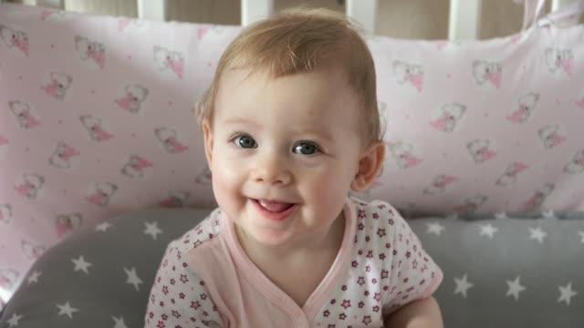 8 månader gammal söt flicka som leker i hennes vit babysäng skratt och leenden - människohuvud bildbanksvideor och videomaterial från bakom kulisserna