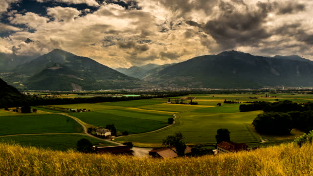 Monthey city and rural valley farmland rain and sunshine video