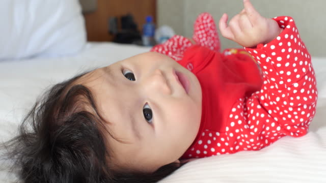 6 months smiling baby girl lying on bed - soltanto neonati video stock e b–roll