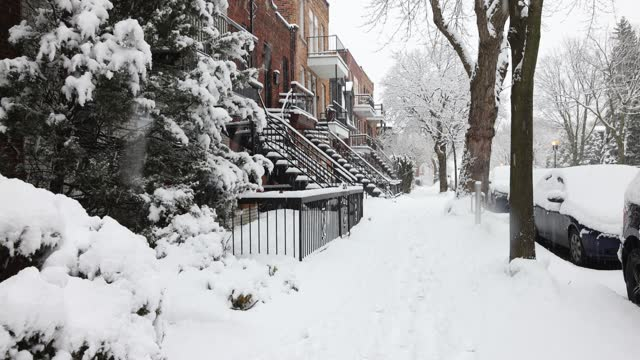 Montreal Rosemont area residential sidewalk early morning during a snow storm
