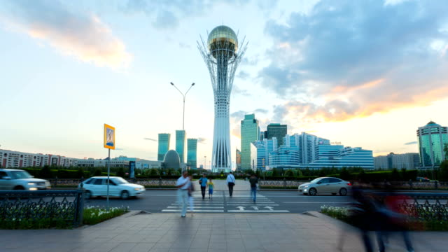 Monument Baiterek in Astana, capital Kazakhstan Astana, Kazakhstan - August 3, 2016: In the center stands the Baiterek monument, on the background of residential houses and offices. Evening time, the sun at sunset. People cross the road, and cars go. kazakhstan stock videos & royalty-free footage