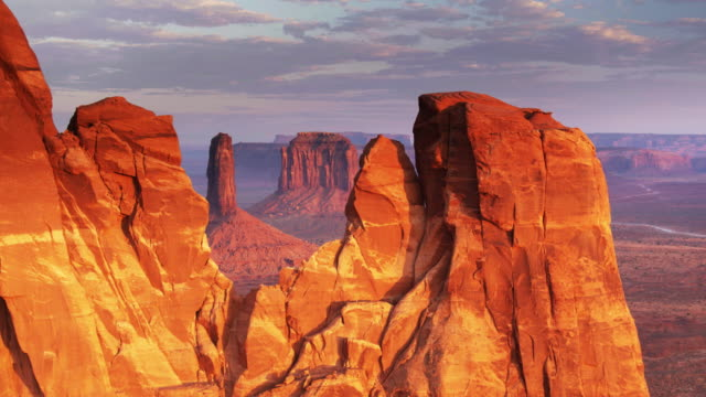 monument valley buttes in red sunset light - drone shot - landscape video stock e b–roll