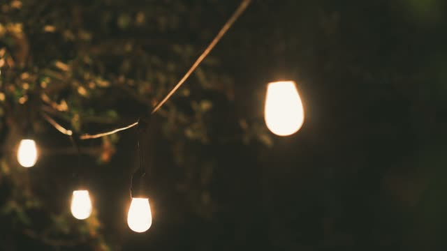 mood lighting - party string lights swinging in slow wind at home garden