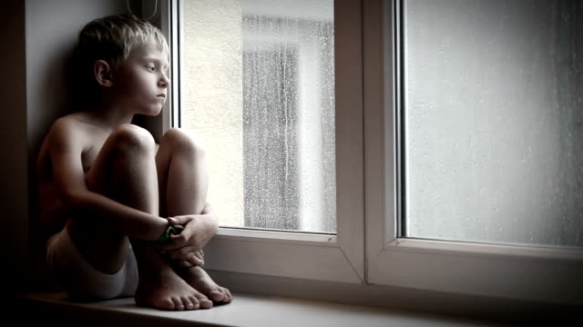 Moody little boy sitting on the windowsill watching raindrops go down the windowglass video