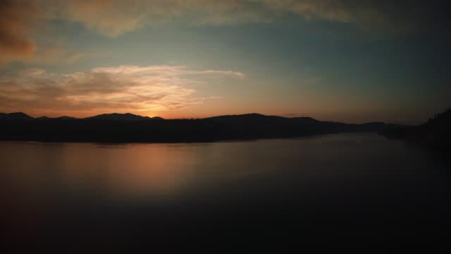 ムーディーシャドウシルエット砂漠の丘は、サンセット空中で湖の水を囲みます ビデオ