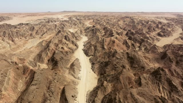 Moonscape Canyon Swakopmund Namibia Aerial 4K Video Aerial Drone 4K Video flying over rural desert gravel road through the surreal Moon Landscape, Moonscape Canyon. Aerial Drone 4K Video. Moonscape Canyon Landscape, Swakopmund, Erongo Region, Namibia. swakopmund stock videos & royalty-free footage