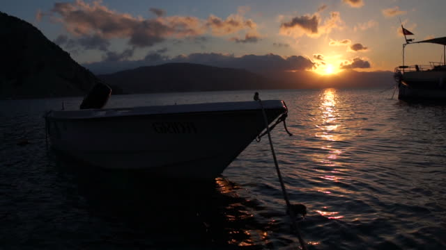 Moored boat at sunset in slow motion