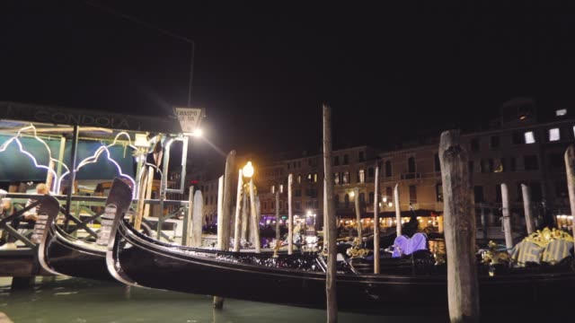 moored gondolas in the grand canal near the rialto bridge at night, several gondolas in a row in the grand canal. grand channel night frame - passenger craft stock videos & royalty-free footage