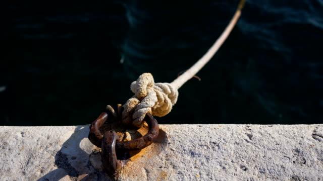 vídeos y material grabado en eventos de stock de amarre de bolardo y cuerda unida a una malla metálica oxidada - amarrado