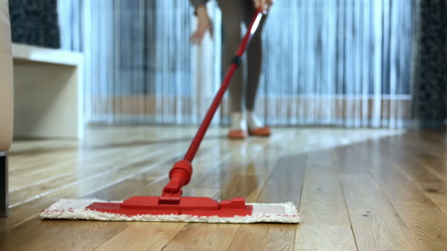 HD DOLLY: Mopping The Hardwood Floor HD1080p: DOLLY shot of a unrecognizable woman mopping the hardwood floor in the living room. cleaning stock videos & royalty-free footage