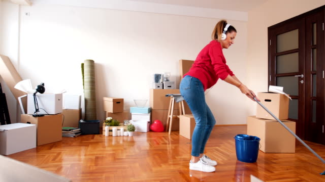 Mopping the hardwood floor There is a one woman, she just bought a new house and she clean the house. mid adult women stock videos & royalty-free footage