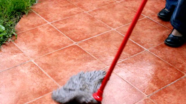 Mopping tiles in garden video