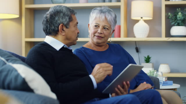 More relaxing, less rushing 4k video footage of a senior couple using a digital tablet and credit card on the sofa at home electronic banking stock videos & royalty-free footage