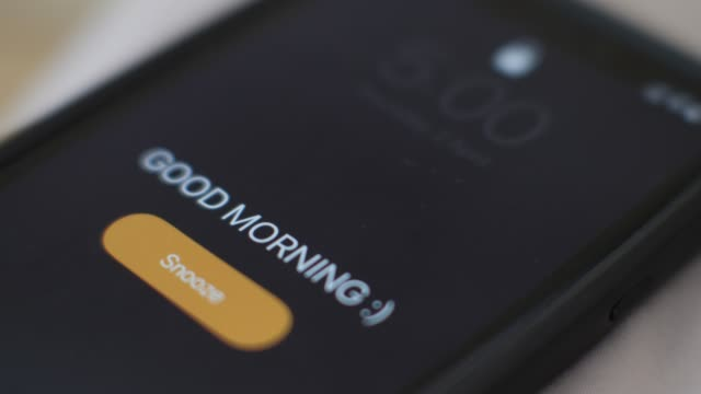 morning alarm clock on the phone in the bed, a hand tapping snooze, close-up - sonnecchiare video stock e b–roll